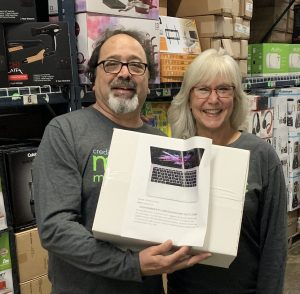 TruStone Financial member and Credit Union Magic Minute™ Loyalty Sweepstakes winner Judy and her husband Tony pose with one of the prizes they grabbed during a 60-second warehouse dash.